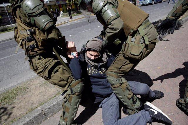 Miembros del cuerpo de Carabineros detienen a un manifestante durante las protestas que están teniendo lugar en diferentes ciudades de Chile en el último mes.