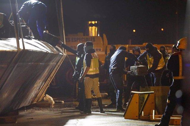 Efectivos policiales y de Aduanas descargan los fardos de cocaína del 'narcosubmarino' localizado en Aldán, en Cangas (Pontevedra)
