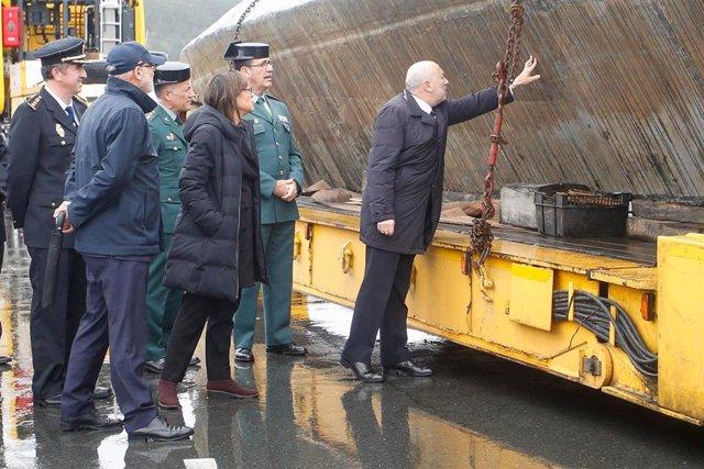 El delegado  Gobierno en Galicia, Javier Losada y la subdelegada,  Maica Larriba, ante el narcosubmarino hundido en Cangas (Pontevedra) y que fue reflotado por dos grandes grúas.
