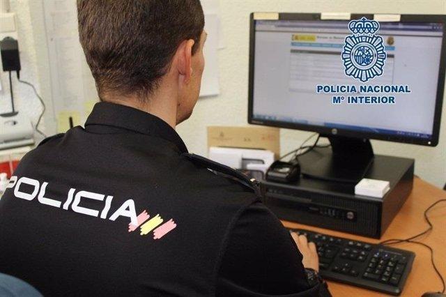 Agente de la Policía Nacional frente a un ordenador