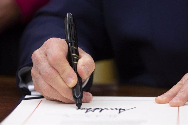Donald Trump firmando la ley de Derechos Humanos y Democracia en Hong Kong.