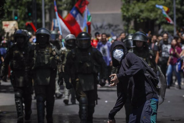 26 November 2019, Chile, Santiago: A masked demonstrator hurls stones while security forces walk towards him during a protest to demanded social reforms. Photo: Sebastian Beltran Gaete/Agencia Uno/dpa