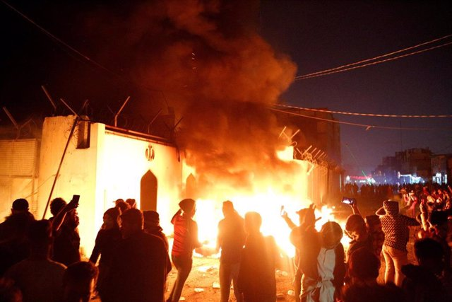 Demonstrators set fire in front of the Iranian consulate, as they gather during ongoing anti-government protests in Najaf