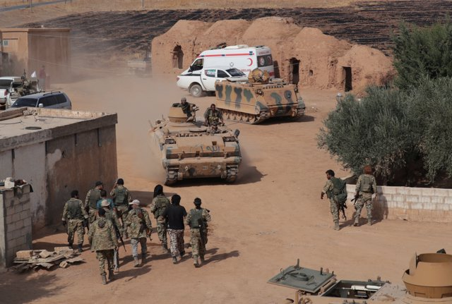 Turkey-backed Syrian rebel fighters drive their military tank near the border town of Tal Abyad, Syria