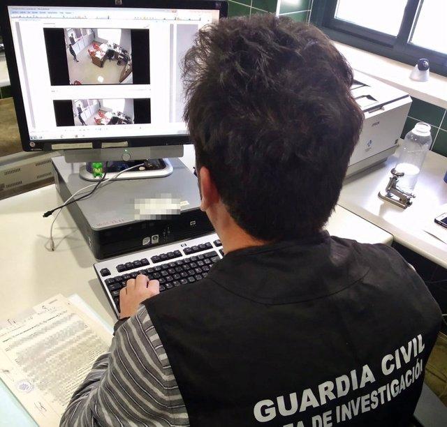 Un agente visiona las imágenes de las cámaras de seguridad de uno de los comercios en los que actuó el detenido.