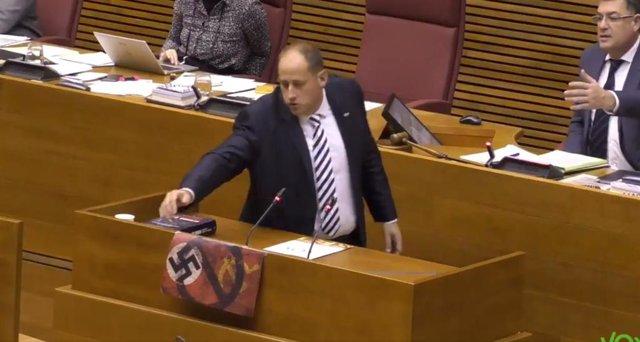 El diputado de Vox David García retira la esvástica colgada en la tribuna de las Costs tras pedirlo el presidente del Parlamento, Enric Morera