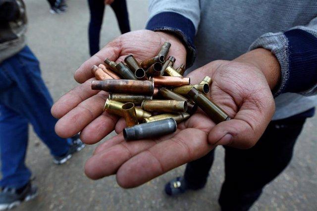 Un manifestante muestra casquillos de bala en Najaf