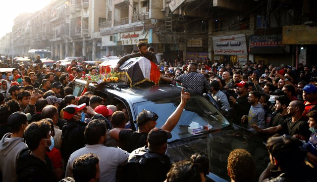 A man holds a coffin of his relative who was killed at an anti-government protest, during the funeral in Baghdad, Iraq