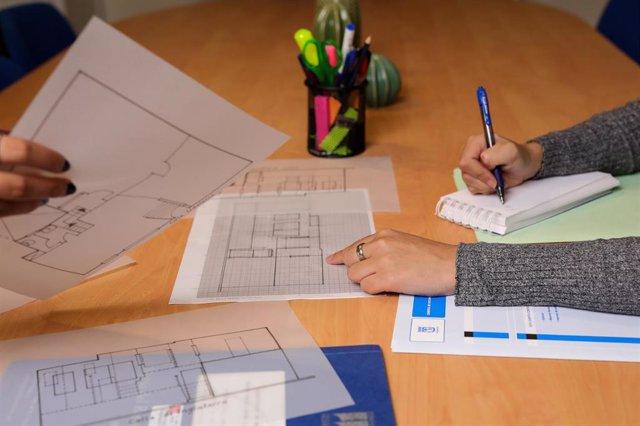 Dos chicas toman notas sobre el plano de una vivienda.