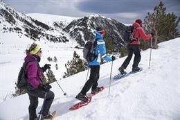 Tres persones pugen una muntanya amb raquetes de neu