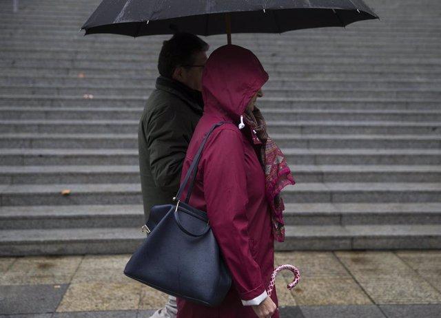 Dos personas caminan bajo la lluvia. En Sevilla, (Andalucía), a 22 de noviembre de 2019.