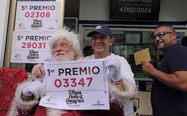 El propietario (con gorra) de la administración de Loteria La Esfinge, de calle Ripoche n1 de Las Palmas de Gran Canaria, celebra, con algunos de los agraciados, que ha repartido parte del Gordo y el quinto premio del Sorteo de Lotería Nacional.
