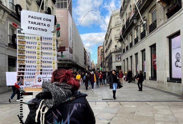 Una mujer decide qué décimo comprar de Lotería de Navidad de la Administración de Doña Manolita, en Madrid (España), a 18 de noviembre de 2019.