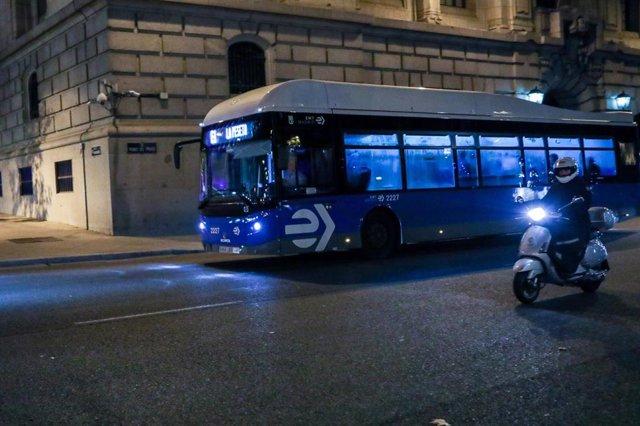 Una moto circula junto a un autobús de la línea E1 en una calle de Madrid.