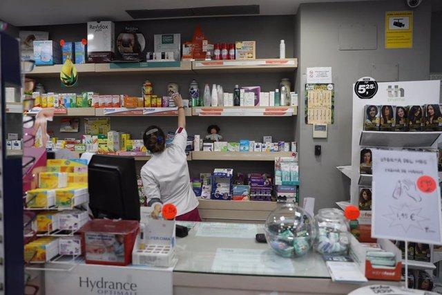 Imagen de una farmacéutica cogiendo un medicamento en una farmacia de Madrid.