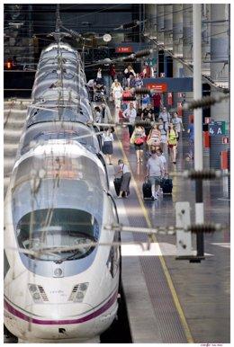 Estació amb un tren d'AVE i viatgers de Renfe.