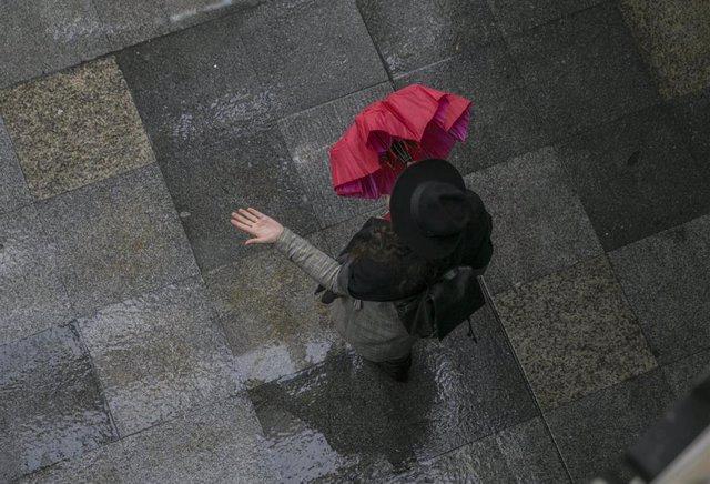 Una mujer comprueba si llueve al salir de una galería comercial.