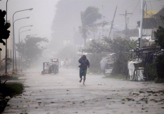 Un hombre caminando en medio de fuertes lluvias en Filipinas.