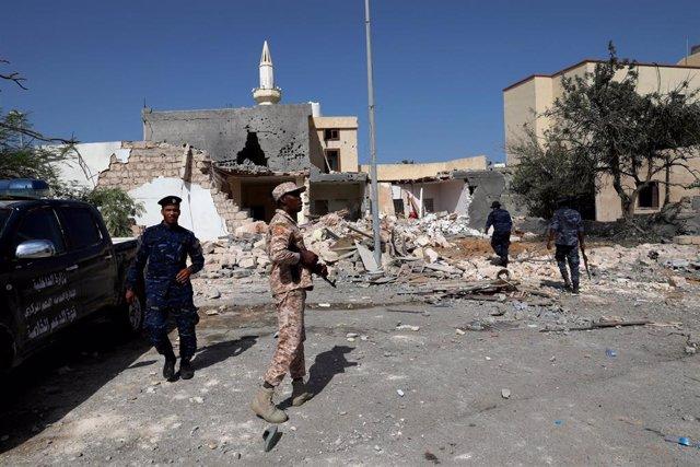 Miembros de seguridad inspeccionan el lugar de un ataque aéreo que golpeó un distrito residencial en Trípoli, Libia