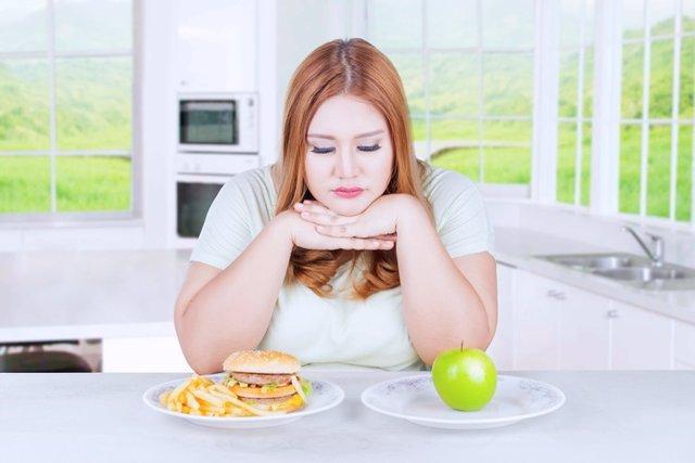 Unhappy woman choosing apple or burger