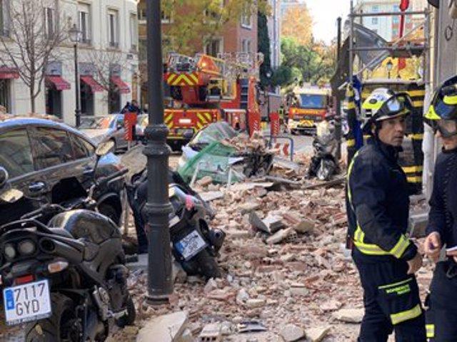 Bomberos de Madrid junto a los restos de la cornisa desprendida de un edificio en obras de Madrid