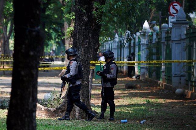 Policías armados hacen guardia después de una explosión en el complejo del Monumento Nacional, en Yakarta (Indonesia)