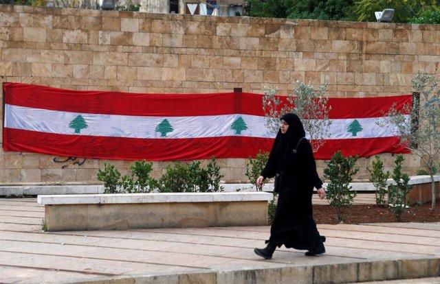Una mujer delante de una bandera libanesa en Beirut