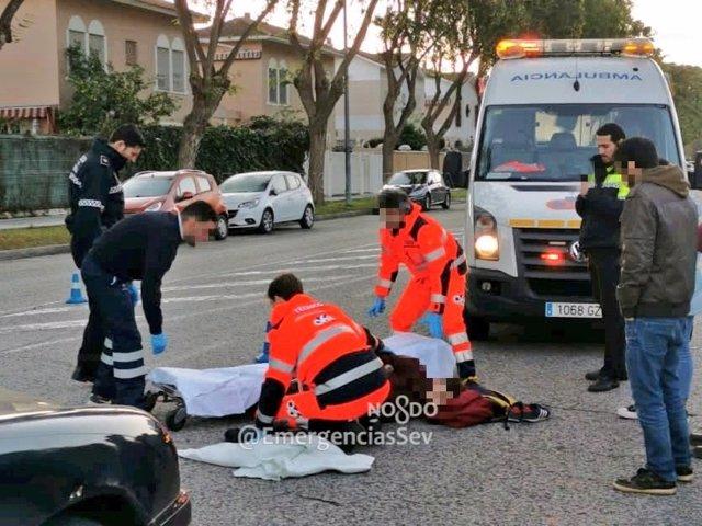 Efectivos sanitarios auxiliar a un joven herido tras ser atropellado en Sevilla capital.