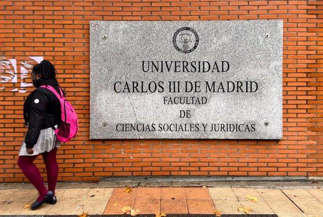 Una chica pasa junto a la placa de la facultad de Ciencias Sociales y Jurídicas del campus de Getafe de la Universidad Carlos III de Madrid, en Madrid a 22 de noviembre de 2019.