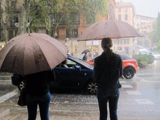 Dos personas con paraguas para cubrirse de la fuerte lluvia en el Paseo del Borne de Palma.