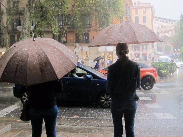 Dues persones amb paraigües per cobrir-se de la forta pluja en el Passeig del Born de Palma.