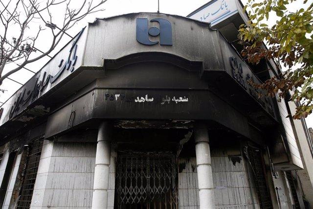 Una sede bancaria después de haber sido incendiada durante las protestas contra el Gobierno de Teherán que se están llevando a cabo en diferentes ciudades iraníes.