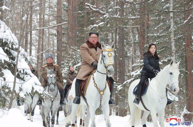 Kim Jong Un montando a caballo en el monte Paektu acompañado por su mujer, Ri Sol Ju, y por altos mandos militares de Corea del Norte