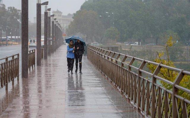 Peatones bajo la lluvia  por el Puente de los Remedios  en Sevilla a 22 de noviembre del 2019
