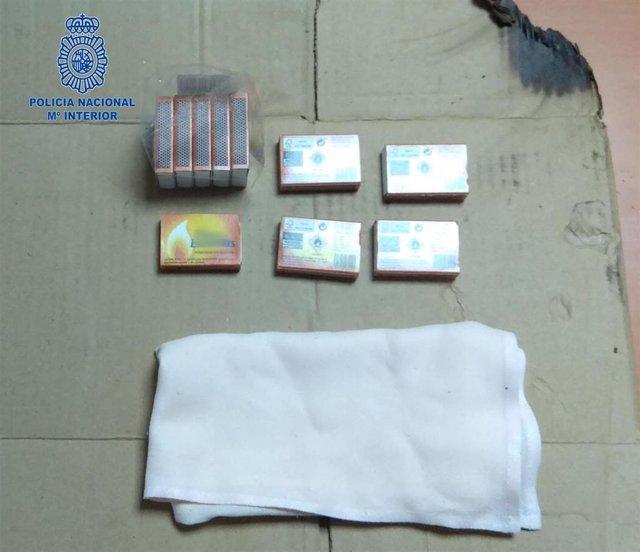 Cajas de cerillas y un cartón quemado con los que presuntamente la detenida se disponía a prender fuego a la puerta de su madre.