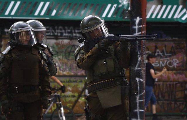 Carabineros apuntan a un manifestantes en Chile