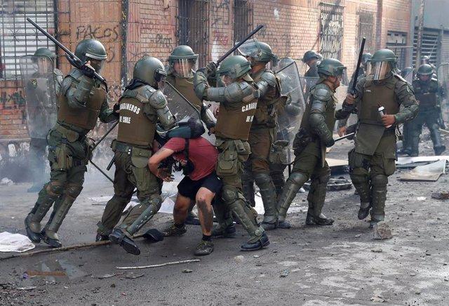 Agentes del Cuerpo de Carabineros reducen a un manifestante durante las protestas en Santiago, Chile.