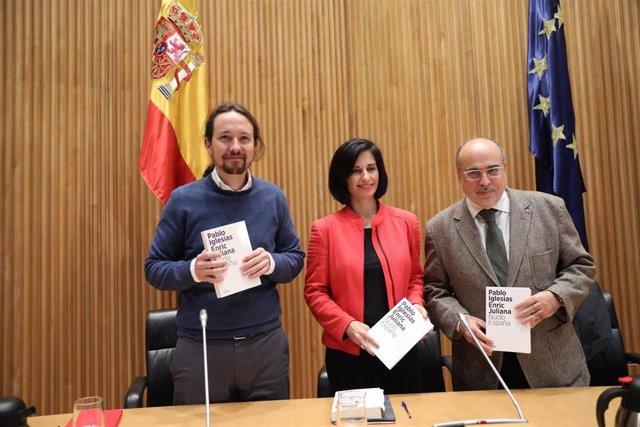 (I-D) El secretario general de Podemos, Pablo Iglesias; la periodista Lola García como moderadora y el periodista Enric Juliana posan con el libro del evento durante el diálogo `Nudo España: un año después en el Congreso de los Diputados