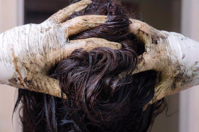Mujer usando tinte permanente para el cabello.