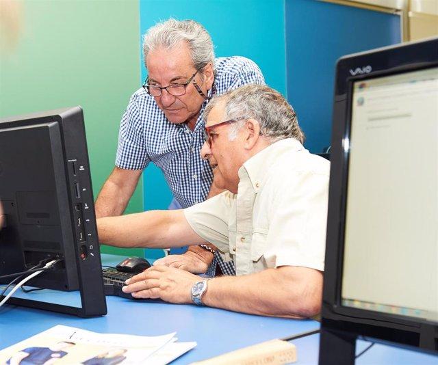 Imagen de dos hombres en una de las actividades para personas mayores sobre informática.