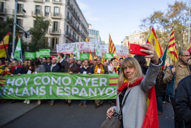 Una assistent a la manifestació per la Constitució a Barcelona es fa una foto davant d'una de les pancartes, que diu 'Avui com ahir, catalans i espanyols', Barcelona (Catalunya/Espanya) 6 de desembre del 2019.