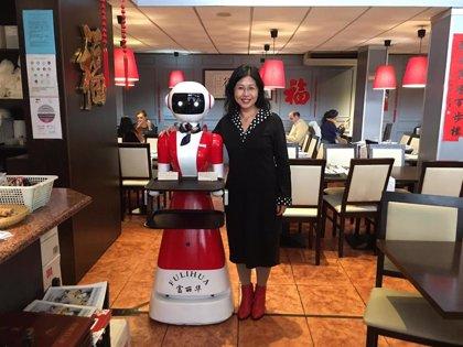 Una camarera robot que dice 'Que aproveche, cariño' a los clientes, atracción de un restaurante chino en Valdebernardo