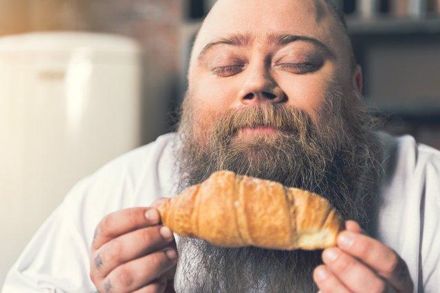 Hombre obeso oliendo un bollo