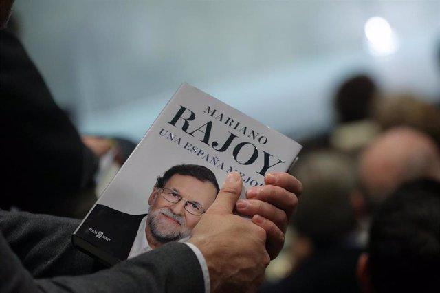 """Una persona sostiene el libro del expresidente del Gobierno Mariano Rajoy, """"Una España Mejor"""", durante su presentación en la Fundación Rafael del Pino, en Madrid a 4 de diciembre de 2019."""