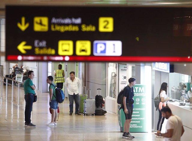 Algunos turistas esperan a ser atendidos en un puesto de cambio de moneda en el Aeropuerto Adolfo Suárez Madrid-Barajas.