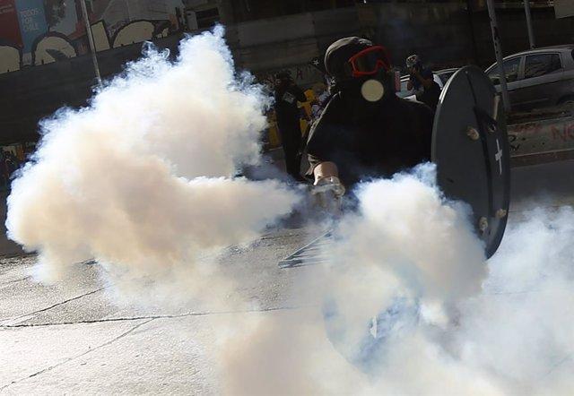 Un manifestant retorna un pot de gasos lacrimgens durant una protesta a Santiago durant el Dia dels Drets Humans.