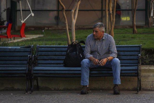 Un hombre sentado en un banco en una calle de Santiago