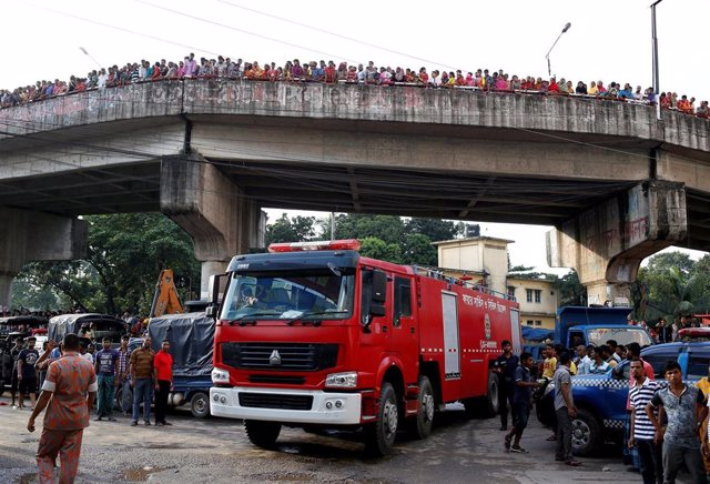 Bomberos junto a una fábrica incendiada en Dacca