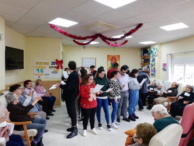Un grupo de jóvenes sevillanos visita a los mayores de un centro de día y canta villancicos por Navidad