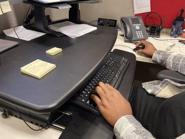 Hombre trabajando en una mesa de escritorio, oficina, ordenador, teclado